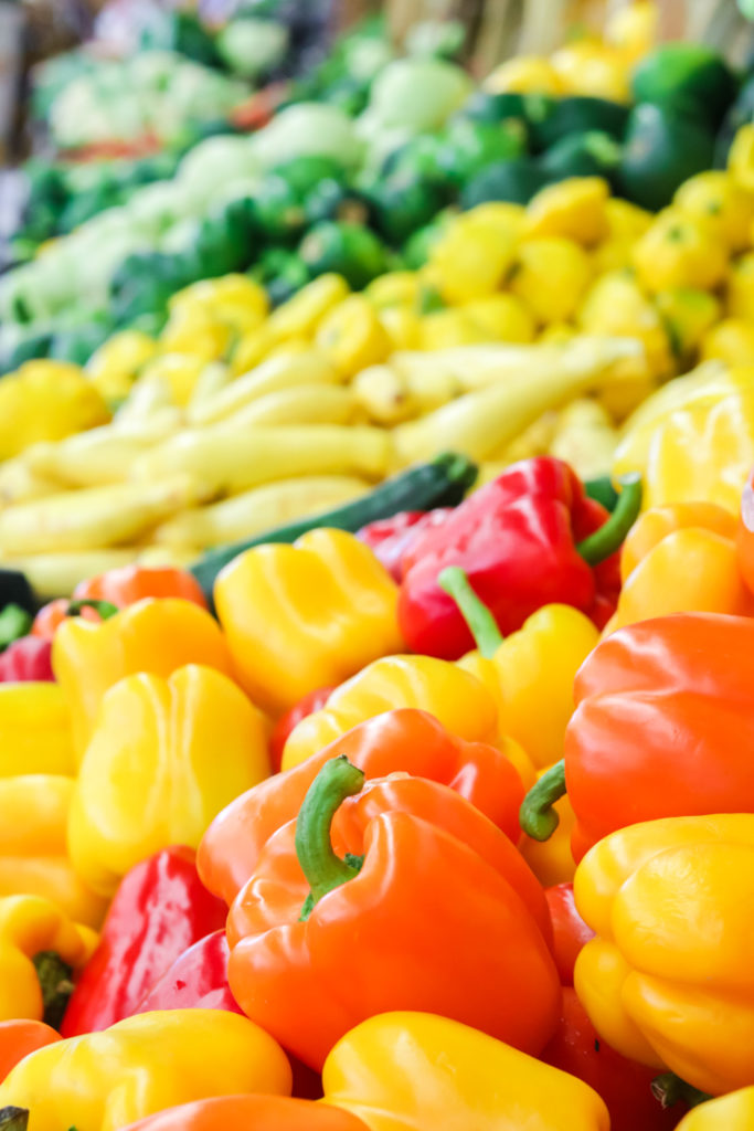rainbow peppers are in season and displayed at a produce stand