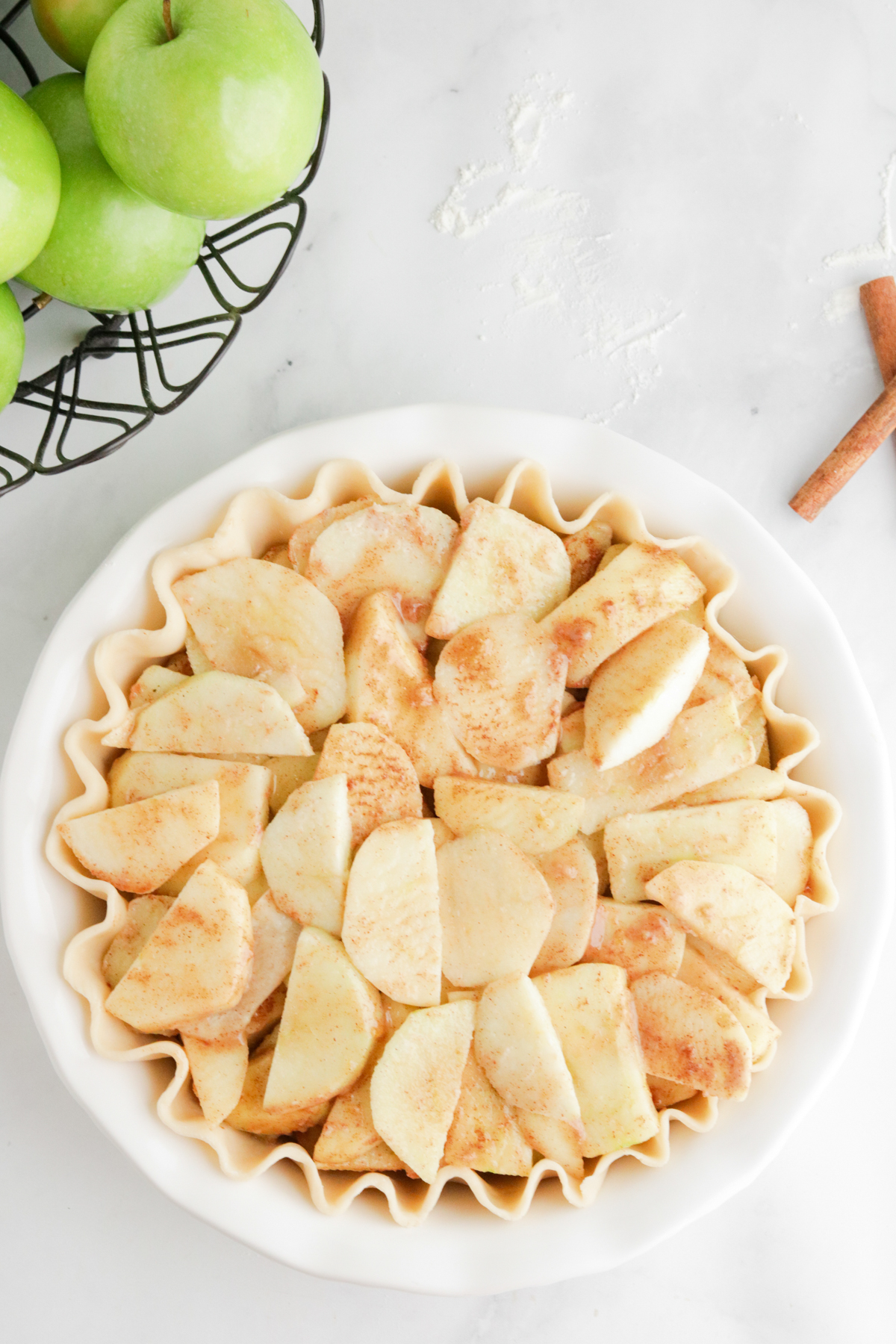 Sugared apples in pie crust to make apple pie with crumble topping