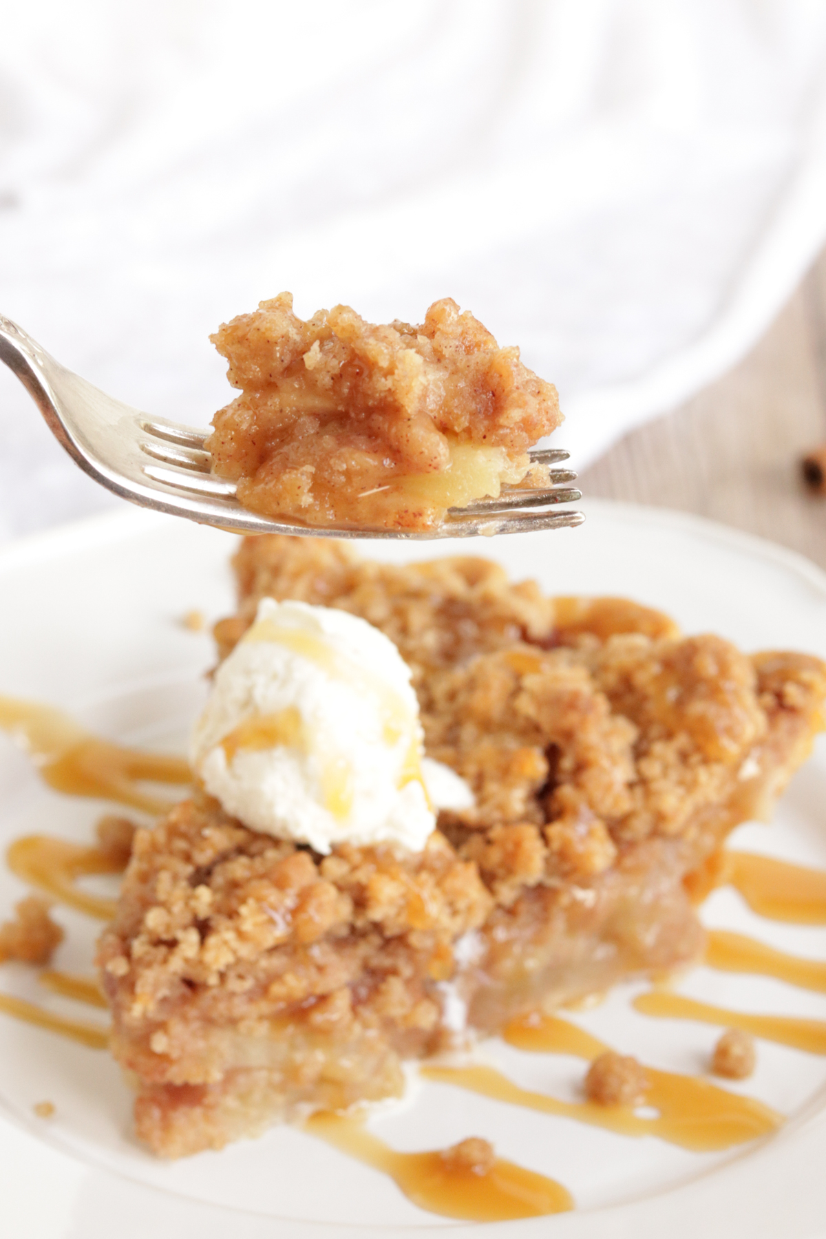A fork with a bite of apple pie over a slice of pie.