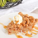 A piece of apple crumble pie on a white plate with ice cream and caramel on top.