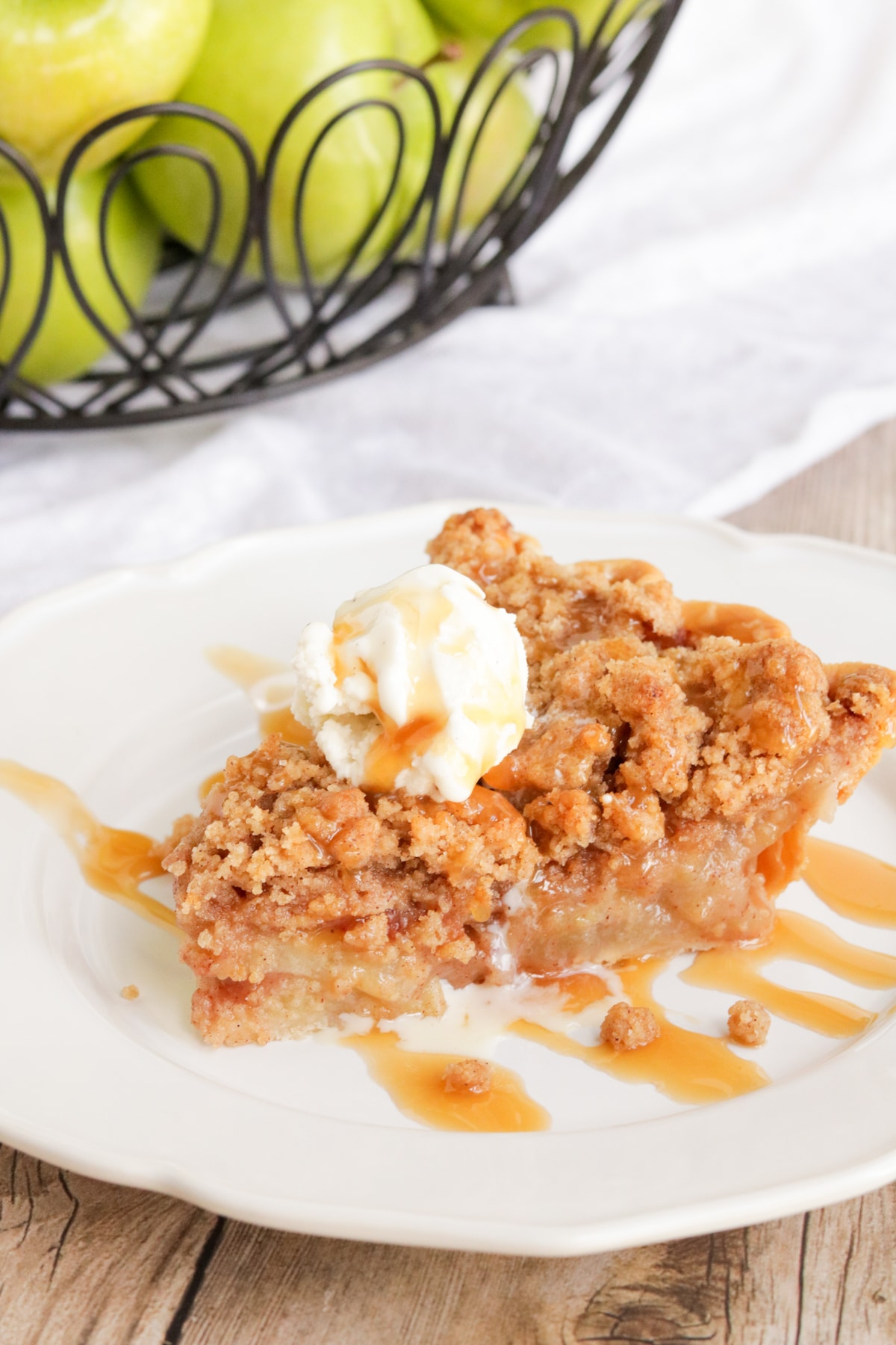 Apple Crumble Pie- a peice of apple crumble pie on a white plate with ice cream and caramel on top.