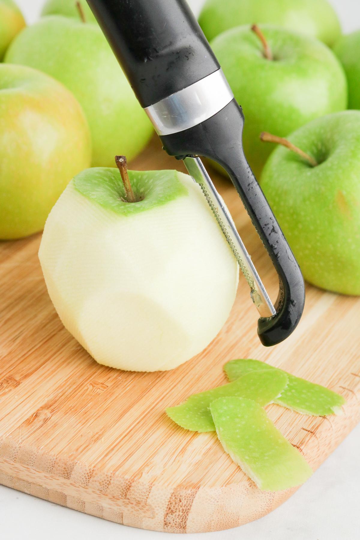 Peeled green apple on cutting board