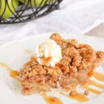 Apple Crumble Pie- a pie slice on a white plate with ice cream and caramel sauce on top.