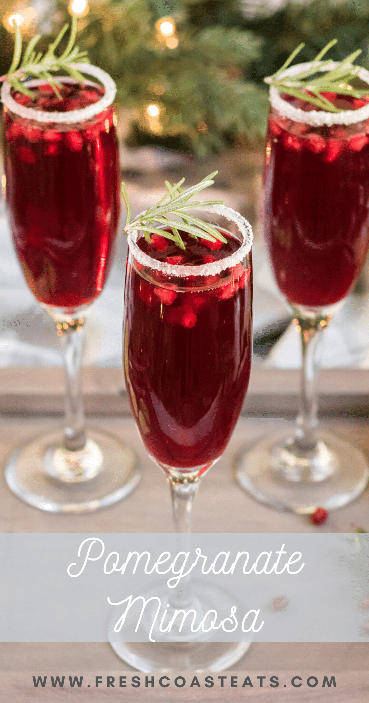 Pomegranate Mimosa- three champage glasses with pomegranate mimosa's. They are garnished with sugared rims and a sprig of rosemary.