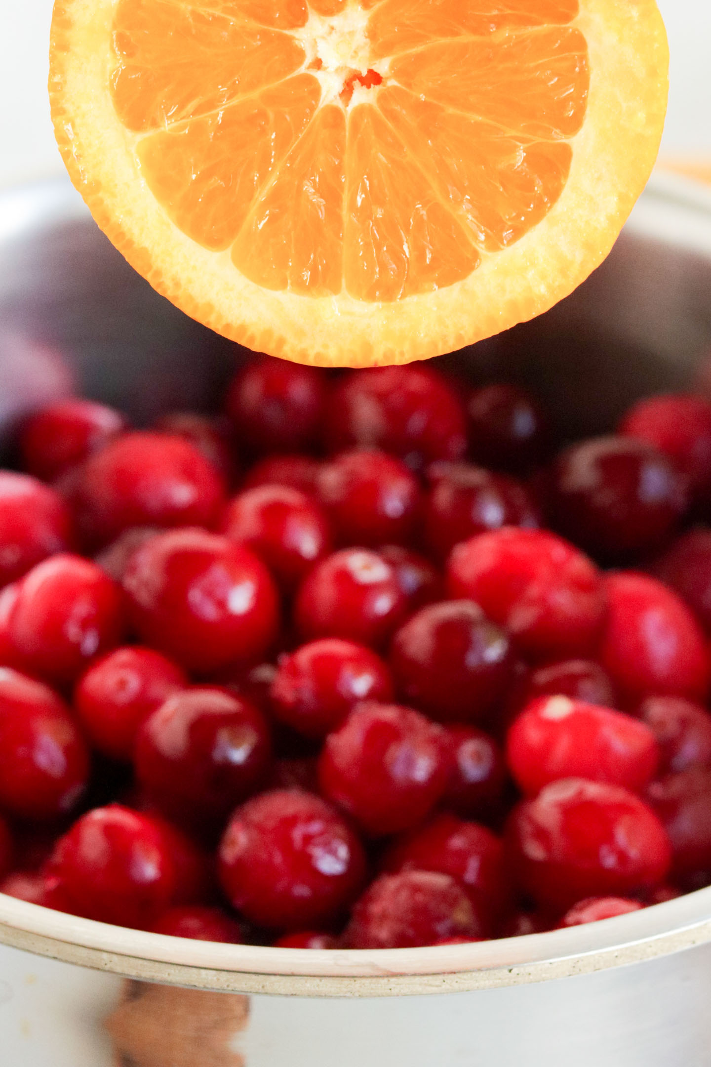 Cranberry Orange Sauce, a close up shot of an orange being squeezed over gresh cranberries.
