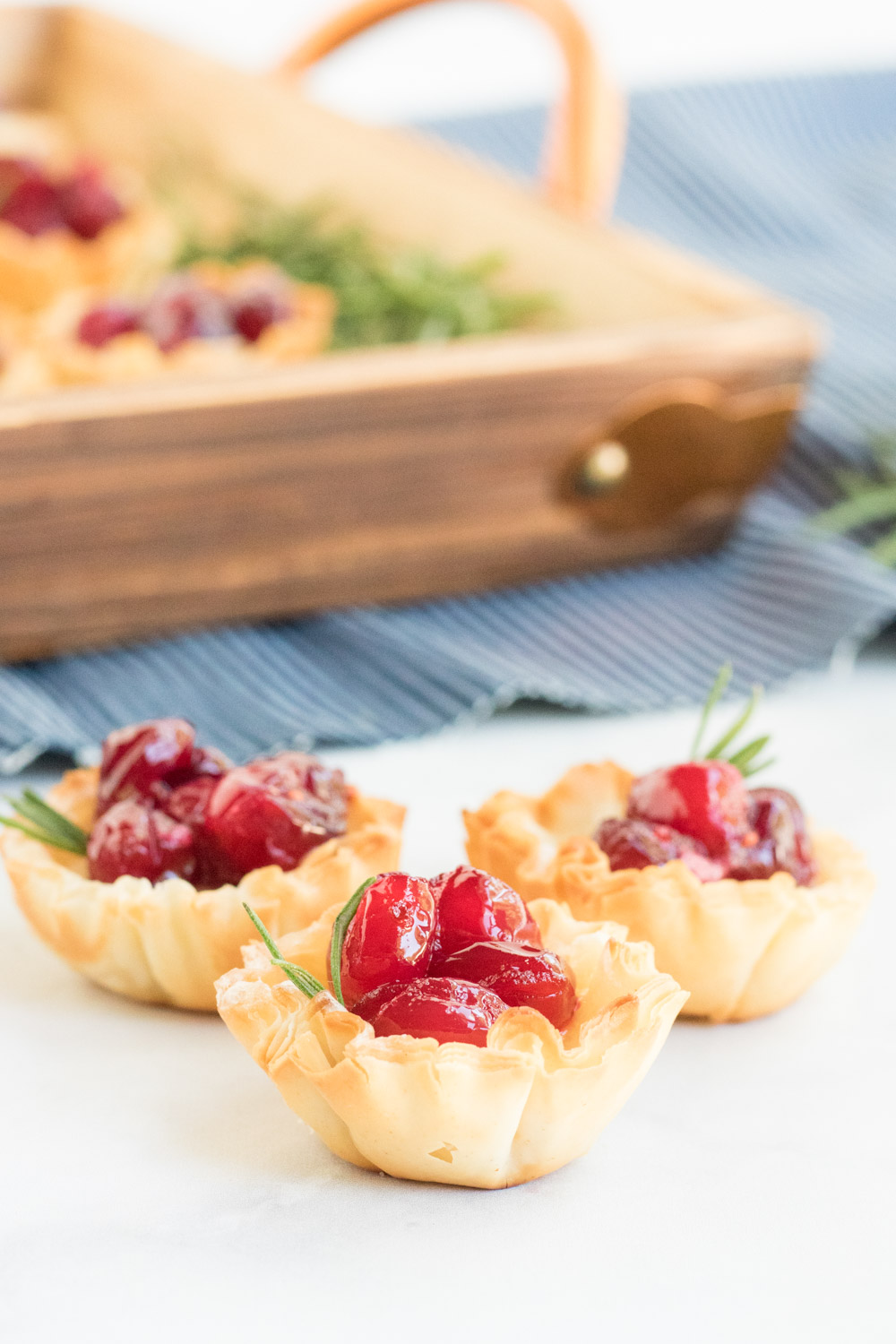Cranberry Brie Bites- picture of a phyllo shell filled with brie cheese and cranberry and a sprig of rosemary