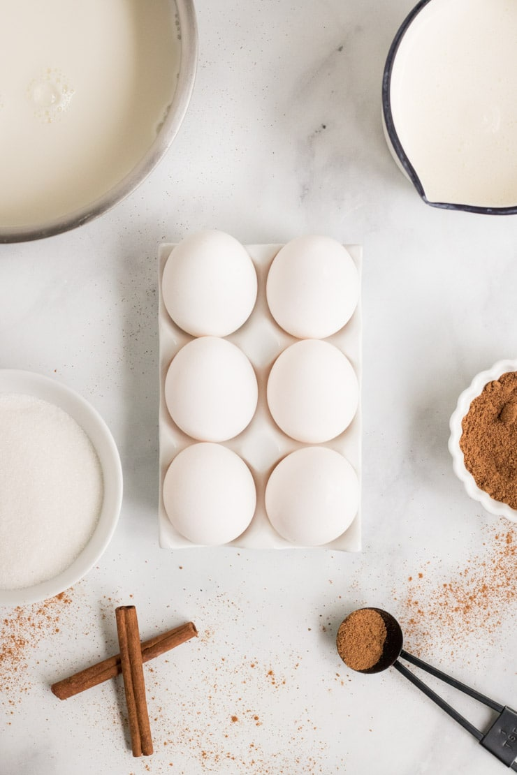Egg Nog Recipe- ingredients laid out to make egg nog. Eggs are in the center with milk, cream and spices.