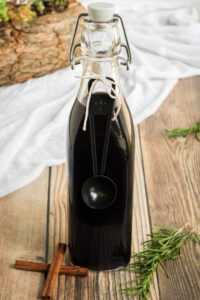 Elderberry Syrup Recipe- a swing top bottle of homemade elderberry syrup