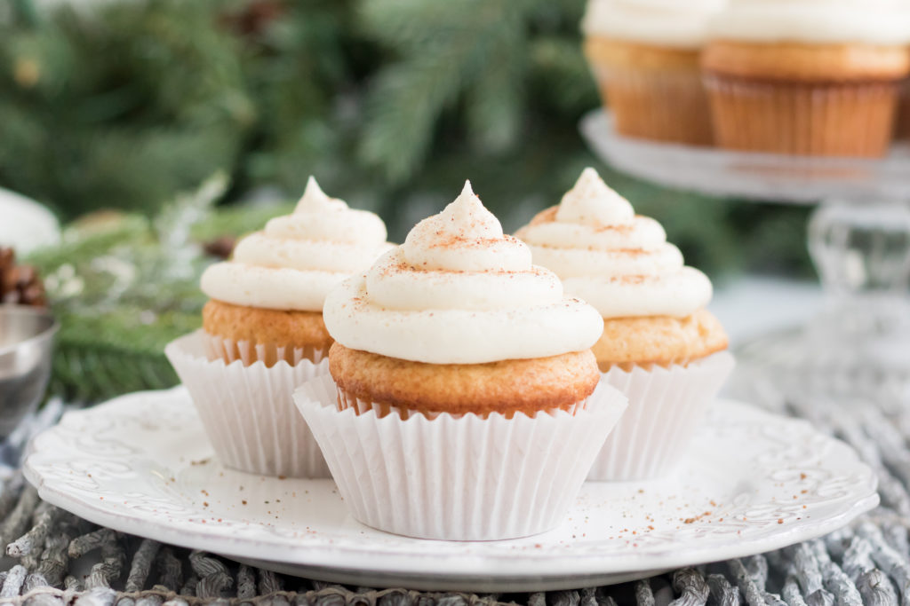 Three vanilla cupcakes on a plate with a garland in the background