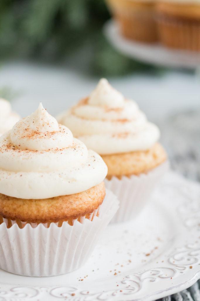 Egg nog cupcake- a close up shot of an egg nog cupcake with a white cupcake liner on a white plate.
