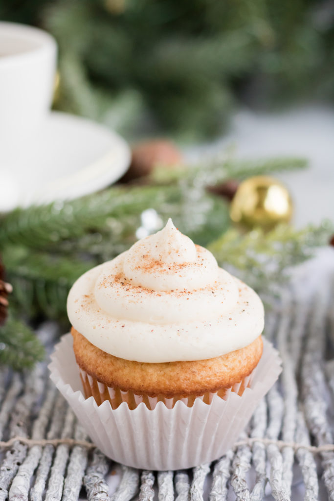 A single eggnog cupcake sits on a birchwood placemat with a garland behind it.