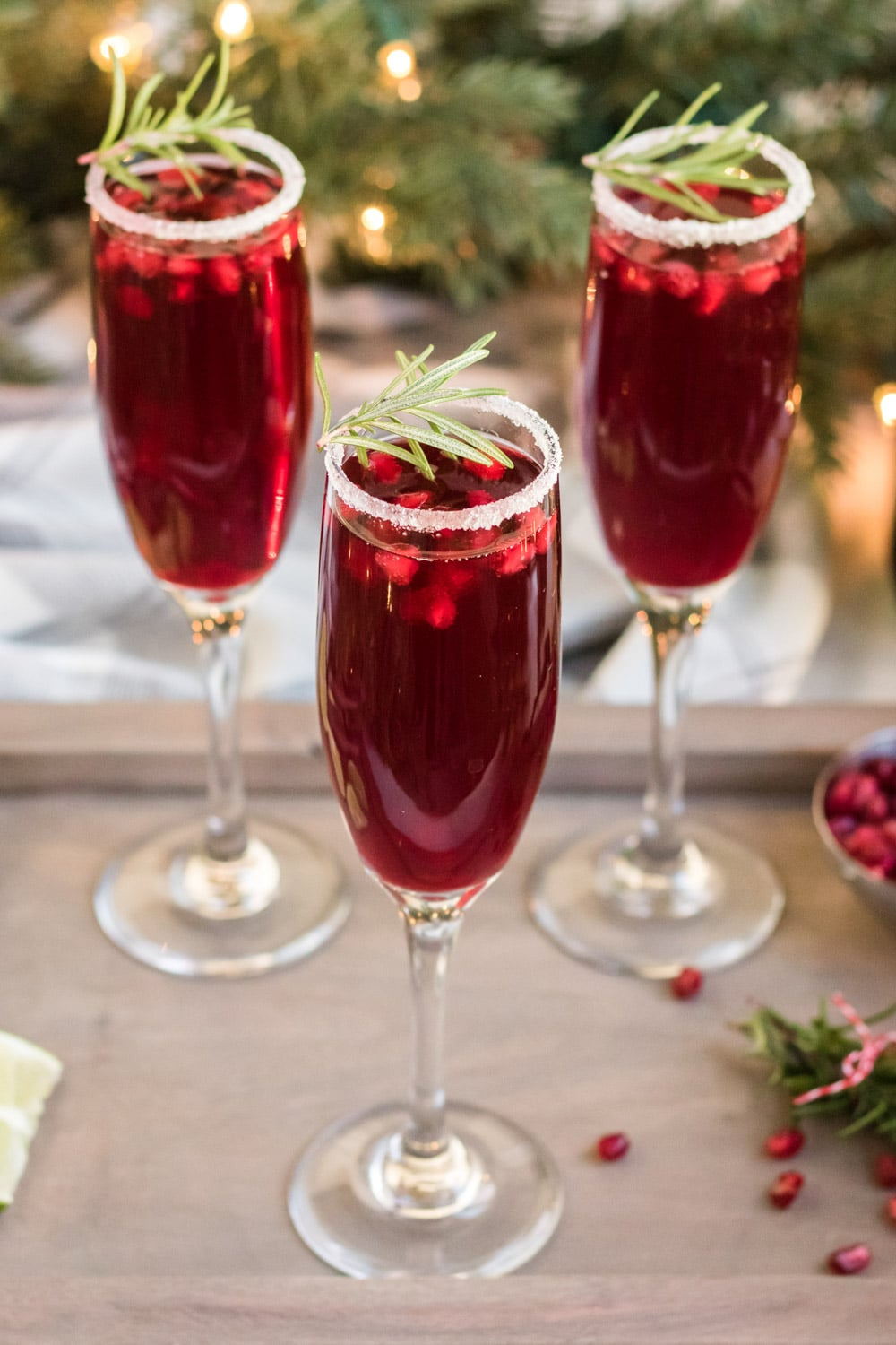 Three champagne flutes with pomegranate mimosa inside. They are garnished with sugar and rosemary.