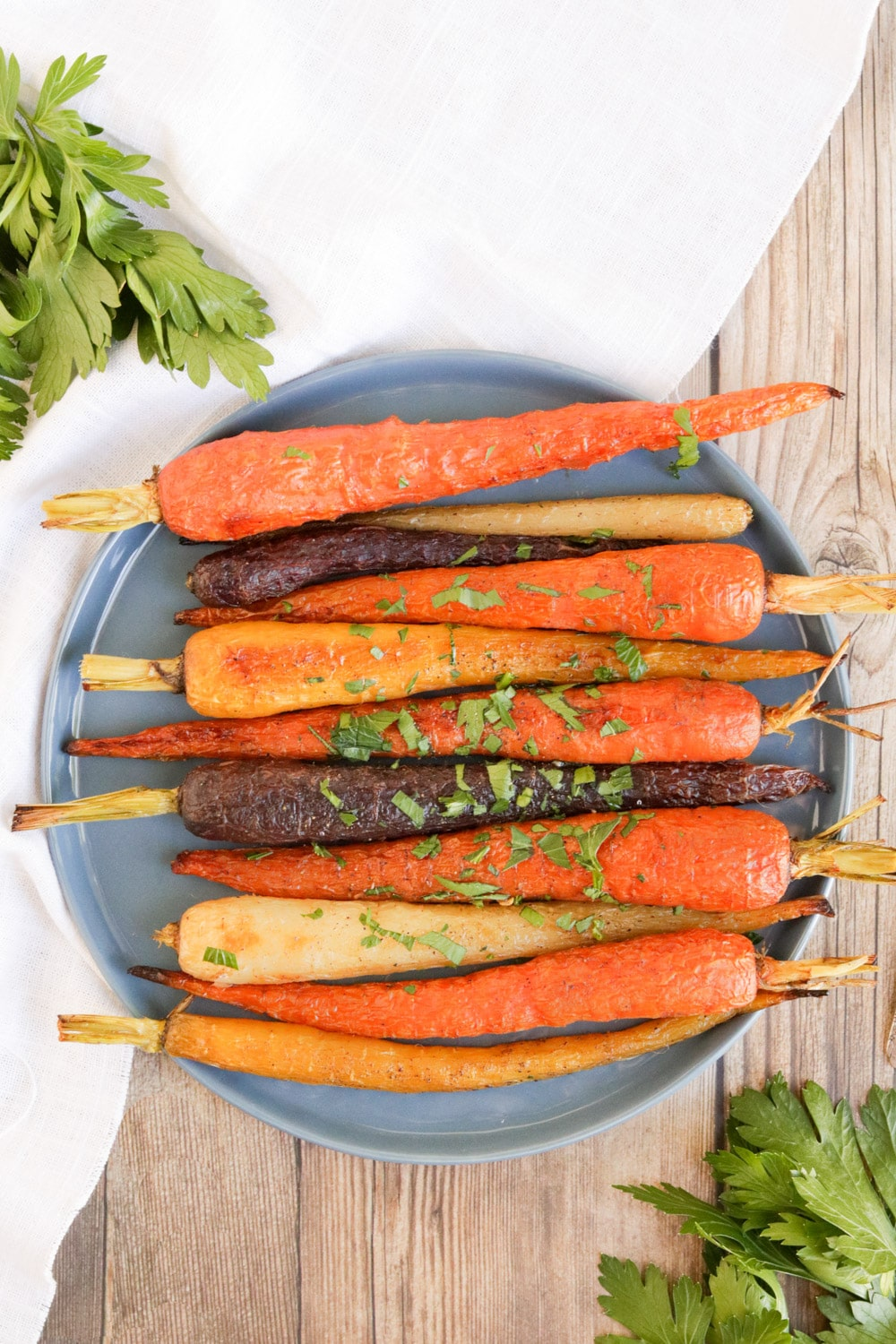 Whole Roasted Rainbow Carrots: Whole Roasted Rainbow Carrots on a blue plate with a white linen.