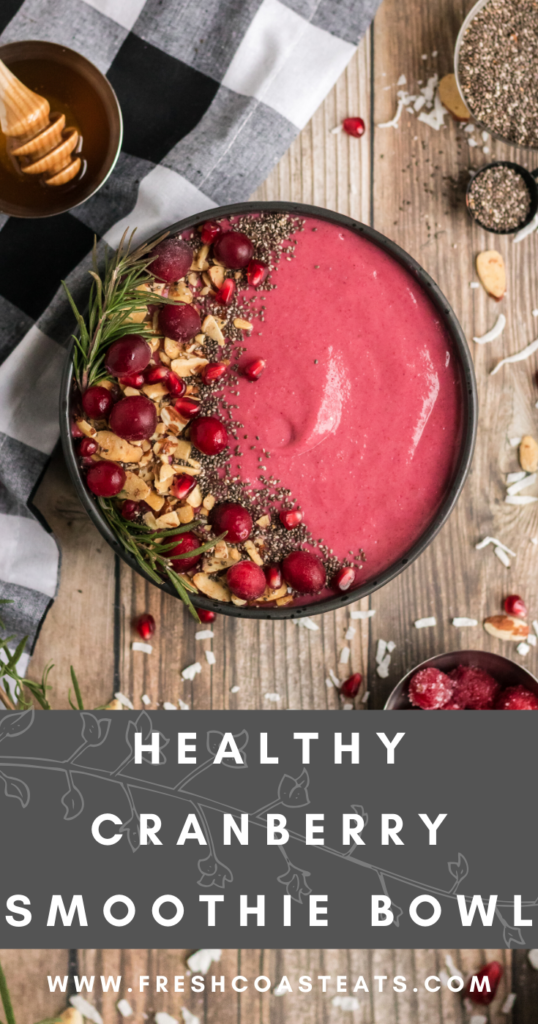 Pinterest image for cranberry smoothie bowl. There is a cranberry smoothie in a black bowl with almonds, chia and cranberries as garnish.