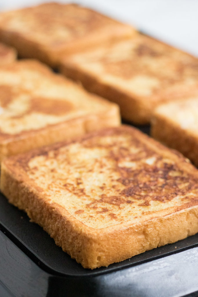 Egg Nog French Toast Recipe- egg nog french toast being cooked on an electric griddle.