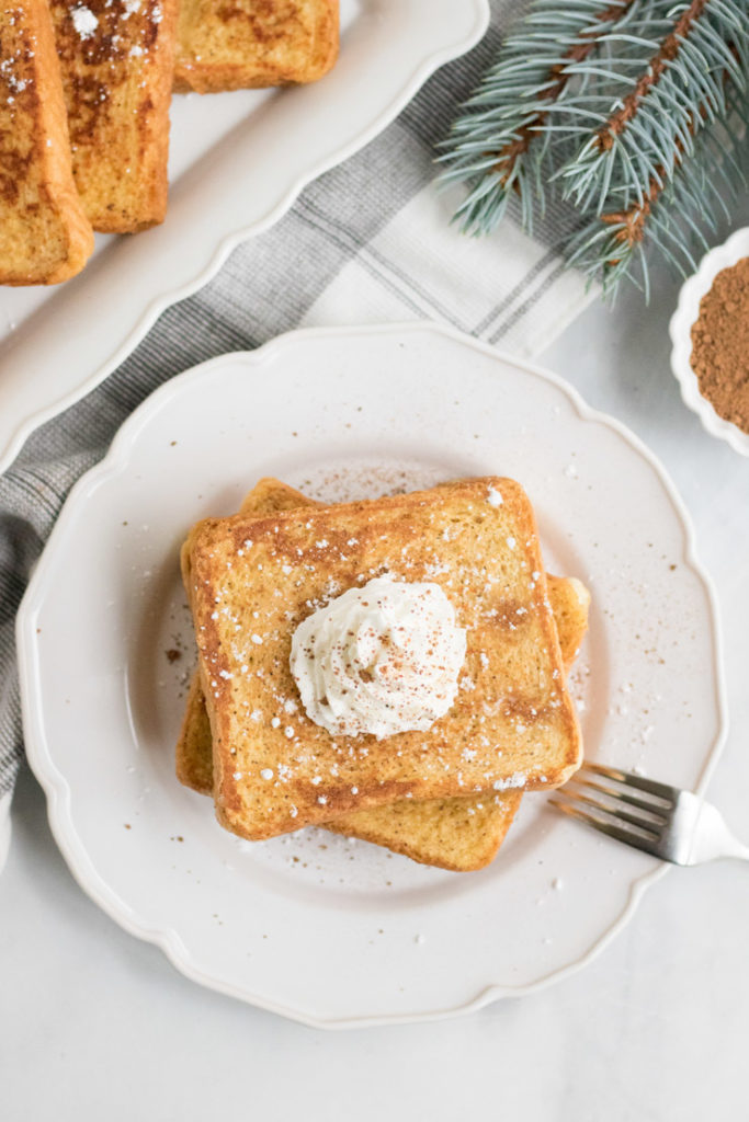 Overhead image of egg nog french toast on a plate with whipped cream