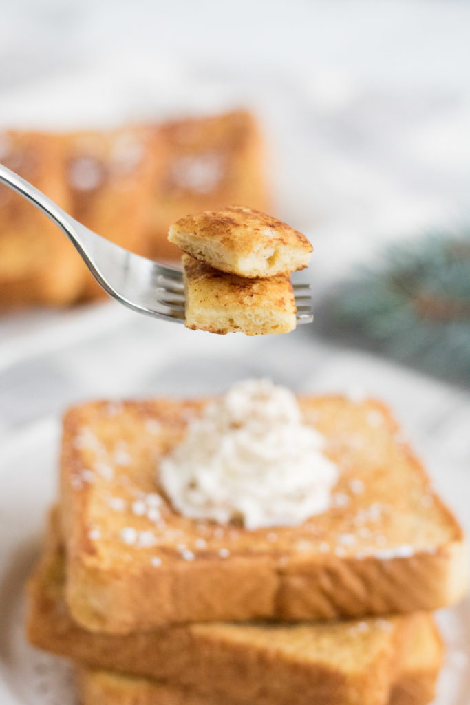 Egg Nog French Toast- a fork with a bite of french toast beind held up above the plate.