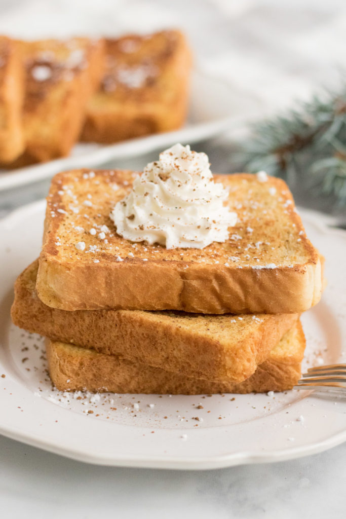 Three pieces of egg nog french toast on a white plate with whipped cream on top.