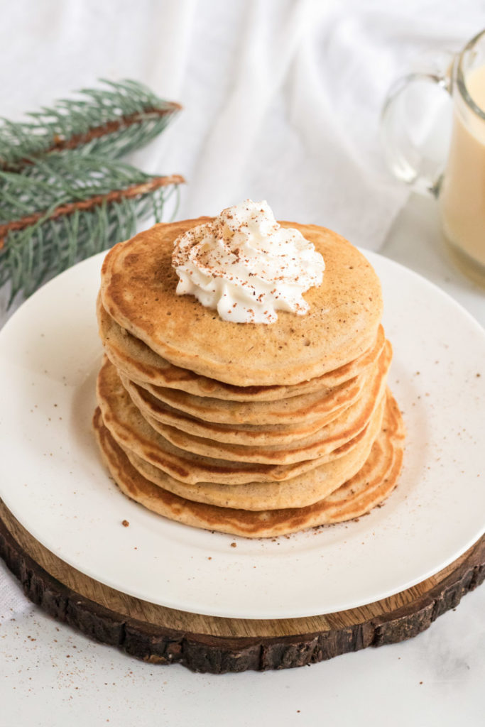 A stack of egg nog pancakes on a white plate on a peice of wood.