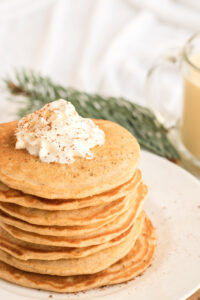A big stack of egg nog pancakes with a bit of whipped cream on top.