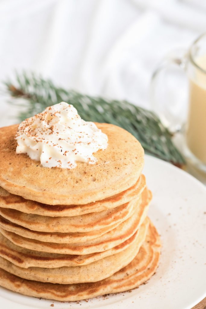A stack of egg nog pancakes with whipped cream and nutmeg on top
