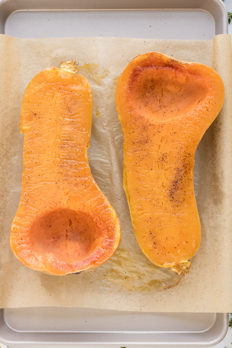 Two roasted butternut squash halves, face up with a little bit of salt and pepper on them.
