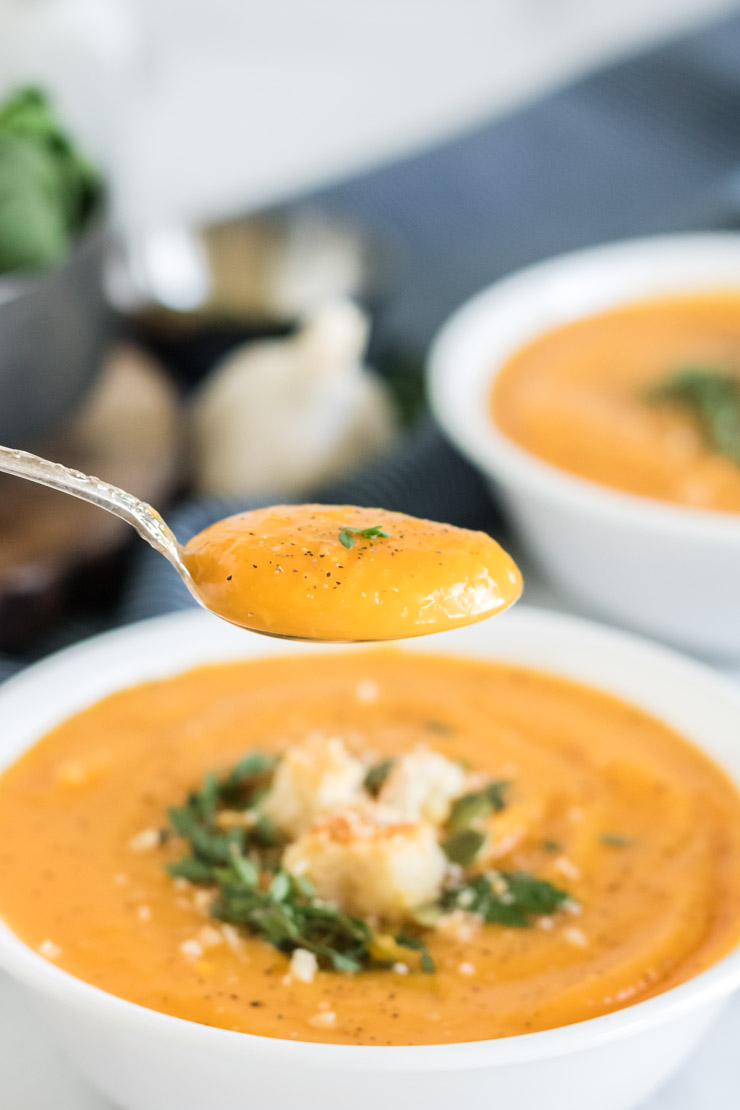 Butternut squash soup in a white bowl with a spoon over the bowl.