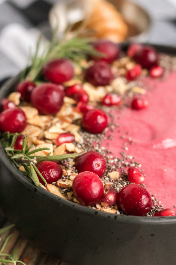 Close up image of a cranberry smoothie bowl with fresh cranberries, chia seeds, almonds and rosemary for garnish.