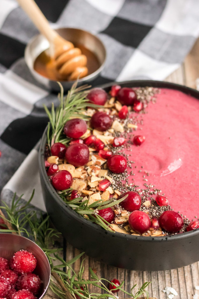 Image of half of a cranberry smoothie bowl with cranberries, almonds, chia seeds and rosemary.