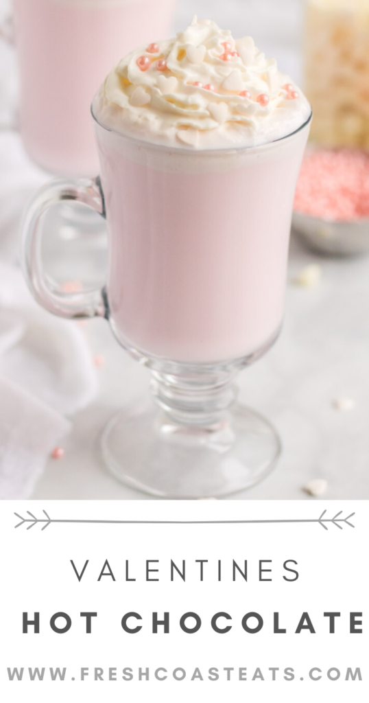Pinterest image for Valentines Hot Chocolate. Pink Hot chocolate is in a tall clear glass mug.