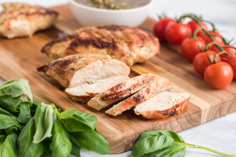 Grilled chicken breasts cut into slices with basil and tomatoes around it.