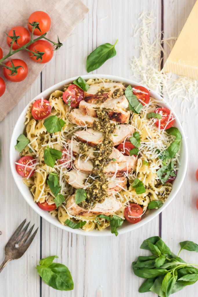 Overhead image of chicken pesto pasta salad in a white bowl with basil and a fork