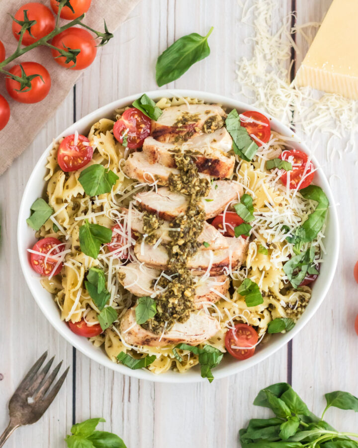 An overhead image of a bowl of chicken pesto pasta salad with basil and tomatoes around it.
