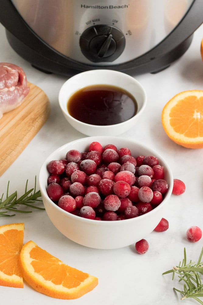Ingredients for cranberry orange pork .Cranberries in a white bowl, orange slices and maple syrup.