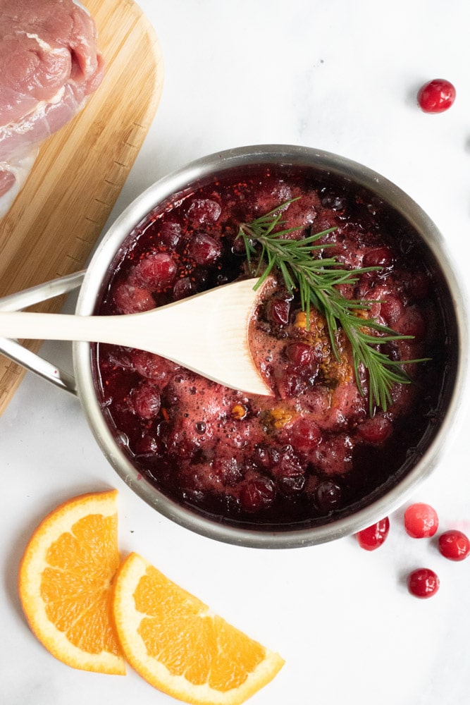 Cranberry Orange Sauce in a small saucepan being made to pour over cranberry orange pork tenderloin.