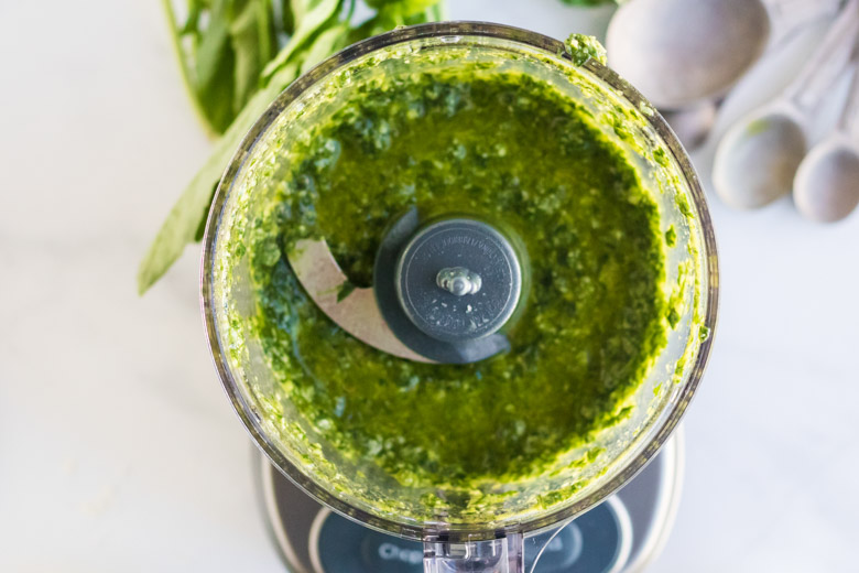 Nut free pesto sauce in a food processor, fully blended.