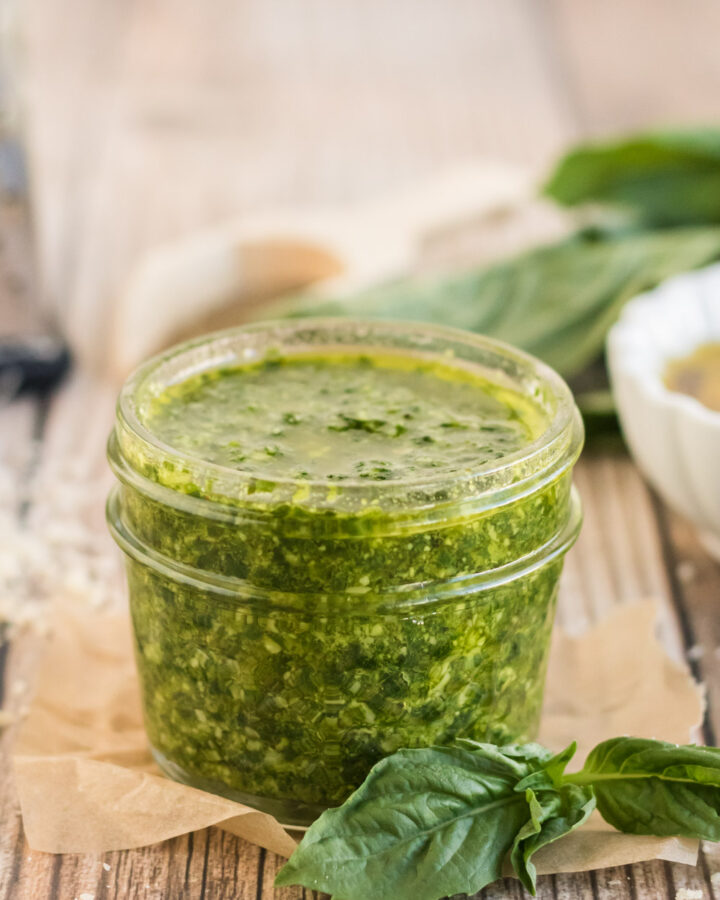Nut free Basil Pesto in a jar with basil leaves around it.