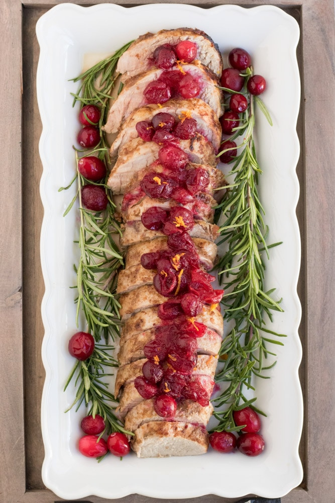 Overhead image of cranberry orange pork tenderloin with cranberries, orange zest and rosemary around it.