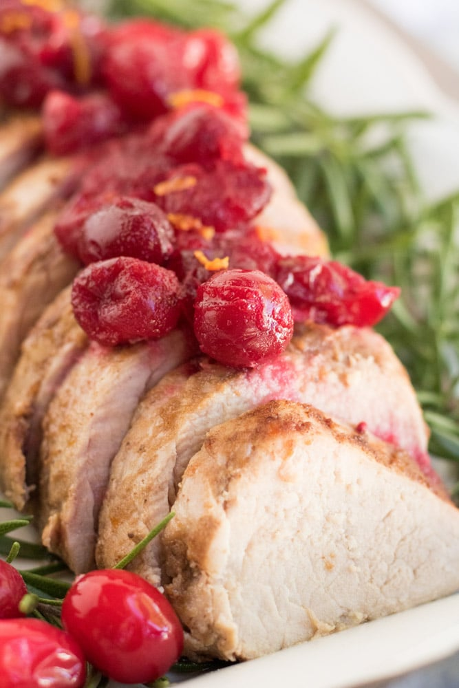 Close up image of pork with cranberries on top and rosemary along the sides.