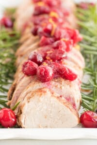 Pork Tenderloin slices in a row with cranberries on top and rosemary on the sides