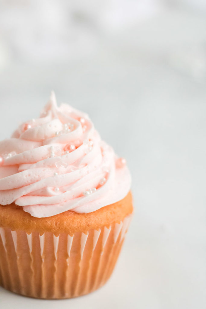 A close up of a pink champagne cupcake with white and pearl sprinkles.