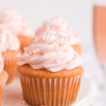 Pink champagne cupcake on a white cake stand with a glass of pink champagne behind it.
