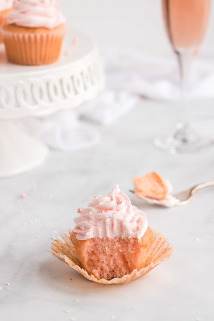A pink champagne cupcake with a bite out of it and a fork behind it.