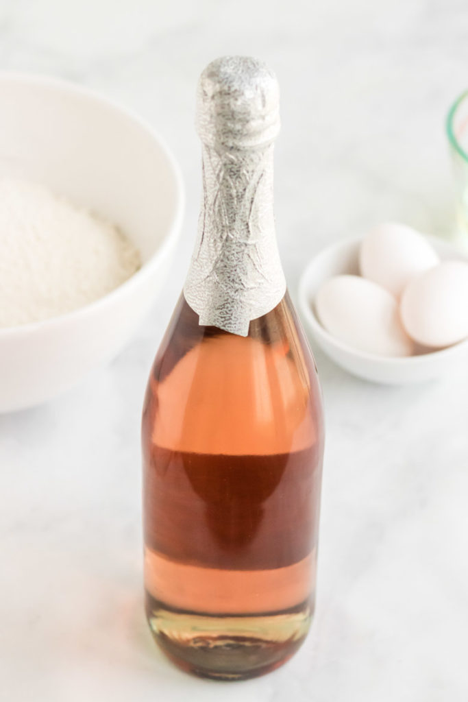 Ingredients for pink champagne cupcakes. A bottle of pink champagne with cupcake ingredients behind it.