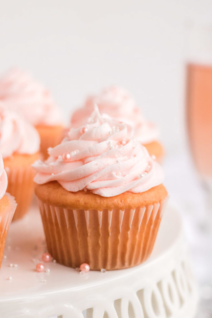 Pink Champagne Cupcake on a Cake stand with a glass of pink champagne behind it.