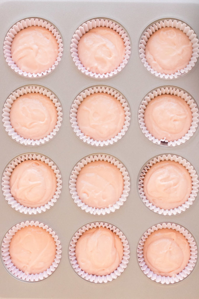 Raw pink champagne cupcake batter in a muffin tin with light pink liners.
