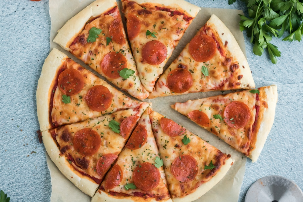 Overhead image of a pizza on parchment paper on a blue slate background.