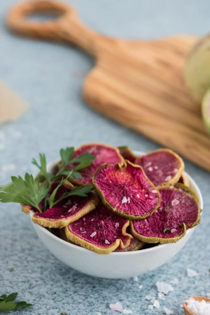 Roasted Watermelon Radish Chips in a light bowl with course salt on a blue background