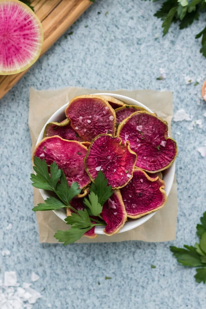 Roasted Watermelon Radish chips in a bowl with a blue background