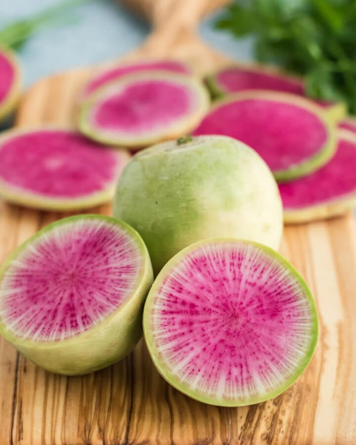 Sliced watermelon radishes on a cutting board with a blue background
